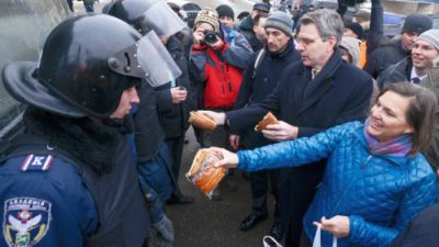 A handout picture released on December 10, 2013 by Ukrainian Union Opposition press services hows US Assistant secretary of State for European and Eurasian Affairs Victoria Nuland (R) distributing cakes to riot policemen on the Independence Square in Kiev on December 10, 2013. (AFP Photo)