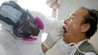 A medical worker, wearing full protective suit, examines a man in an earlier outbreak scare in China in 2003. Photo: Reuters