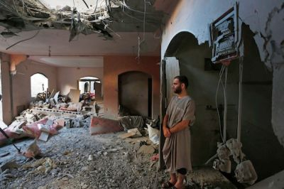 A relative inspects a Palestinian family's apartment, destroyed by an Israeli strike in Beit Lahiya on July 19. AP/Lefteris Pitarakis